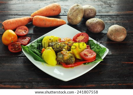 A piece of flank steak baked with vegetables isolated on wood background with vegetables - stock photo