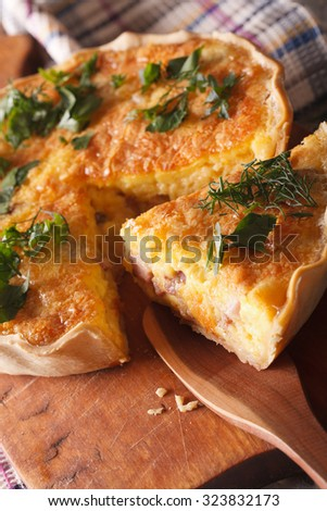A piece of French quiche Lorraine close-up on a cutting board. vertical