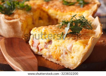 A piece of French quiche Lorraine on the cutting board macro. horizontal