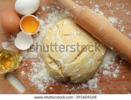 A piece of fresh yeast dough. On a wooden board are dough, eggs and sunflower oil in a glass. In yeast dough is rolling pin.
