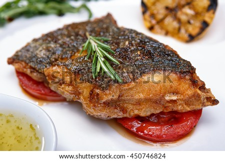 A piece of fried fish with tomato and sauce