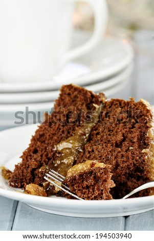 A piece of German chocolate cake on a plate. Shallow depth of field with selective focus on bite on the fork. - stock photo