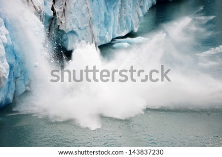 A piece of ice falling from the Perito Moreno glacier in Argentina with the splashes of water - stock photo