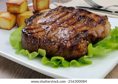 A piece of juicy pork steak grilled with roasted potatoes - stock photo