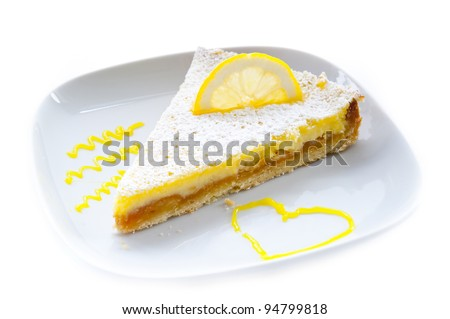a piece of lemon cake, decorated with a slice of lemon on a white plate decorated with a heart on a white background