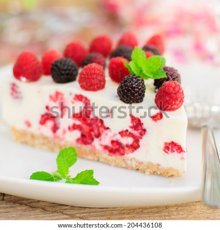 A Piece of No-bake Fresh Raspberry Cheesecake with Red and Black Raspberries and Melissa, Summer Cake, square, close up - stock photo