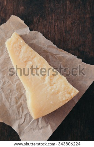 A piece of Parmesan cheese on paper Top view - stock photo