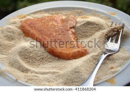 A piece of pork, beaten eggs and breadcrumbs, during the preparation of a Wiener Schnitzel - stock photo