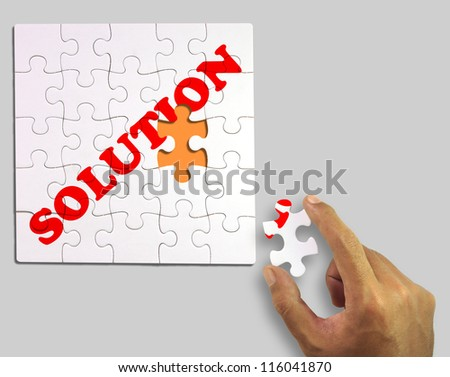 A piece of puzzle in hand. to complete the word solution (Clipping Path) - stock photo