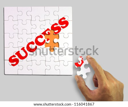 A piece of puzzle in hand. to complete the word success (Clipping Path)