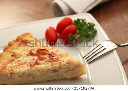 A piece of Quiche on a white plate - stock photo
