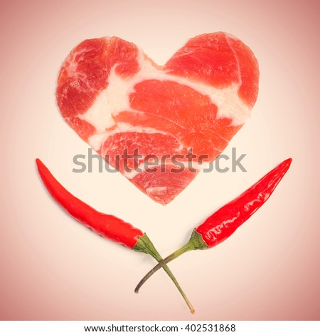 A piece of raw meat in the form of heart and two red chili peppers with green stems. Toned - stock photo