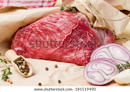 A piece of raw meat in wrapping paper, pepper, onion and thyme - stock photo
