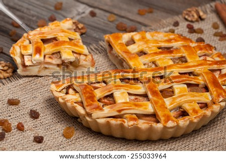 A piece of sliced apple pie with nuts and cinnamon on metal spatula - stock photo