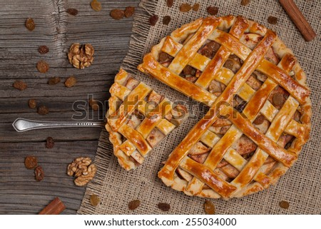 A piece of sliced apple pie with nuts and cinnamon on metal spatula on vintage wooden background texture. Top view - stock photo