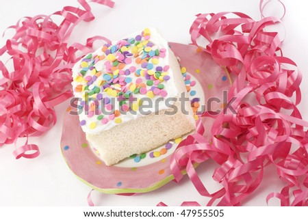 A piece of spring white party cake with pastel colored sprinkles and pink ribbons on a horizontal background with copy space - stock photo