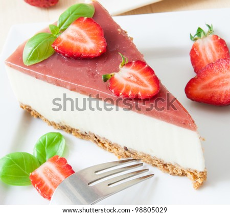 a piece of strawberry cheesecake on white tray with coffee cup