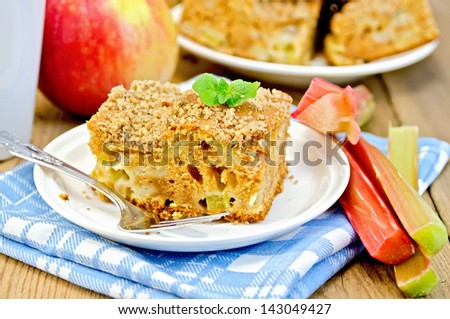A piece of sweet cake with rhubarb and apples, mint, blue napkin, cup on the background of wooden boards
