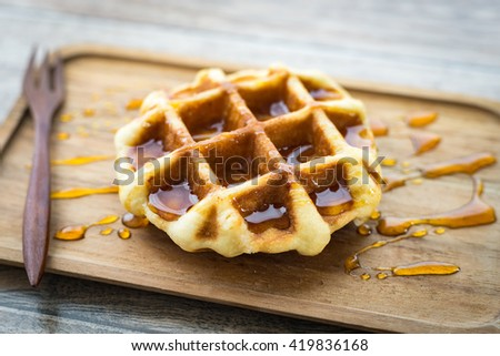 A piece of waffle with honey on wooden plate