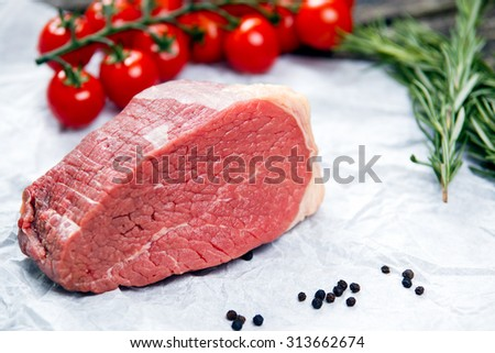 a pieces of fresh meat, beef slab, decorated with greens and vegetables. - stock photo