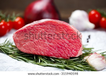 a pieces of fresh meat, beef slab, decorated with greens and vegetables - stock photo