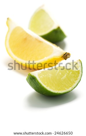 A pieces of lime and lemon isolated on a white background. Background blurry.