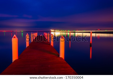 A pier and the Chesapeake Bay Bridge at night, in Kent Island, Maryland. - stock photo