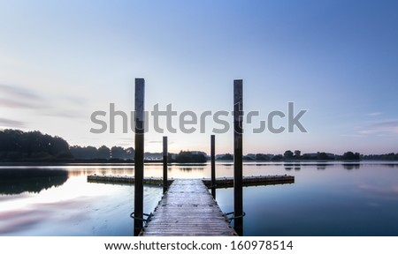 A Pier at sunrise on a lake.