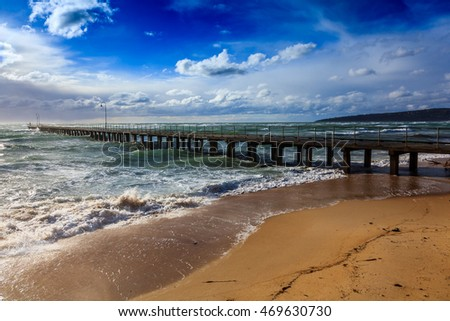 A pier in an amazing light with a windy and harsh sea visible.
