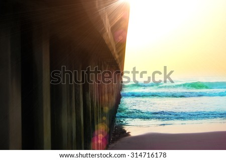 a pier of Durban South Africa leading into the ocean with sunny backdrop - stock photo