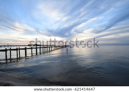 a pier stretches off into the distance framed by a golden sunset that is reflected in the calm ocean