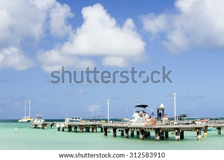 A pier with boats off Aruba's Palm Beach. Beautiful water and skys. - stock photo