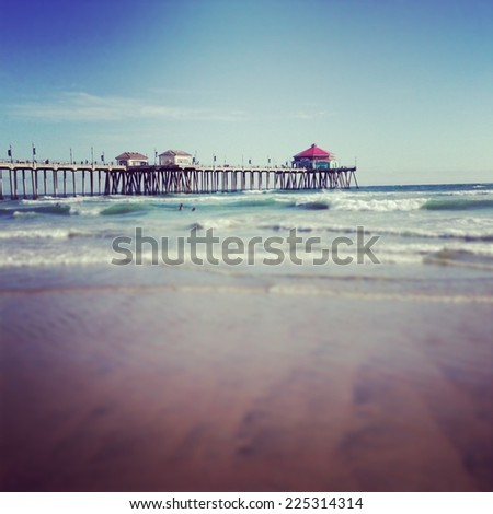 A pier with lots of people on it at the ocean. - stock photo