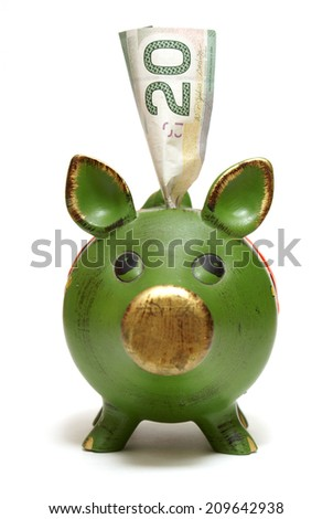 A piggy bank with a twenty dollar bill for the money saving mind set. - stock photo