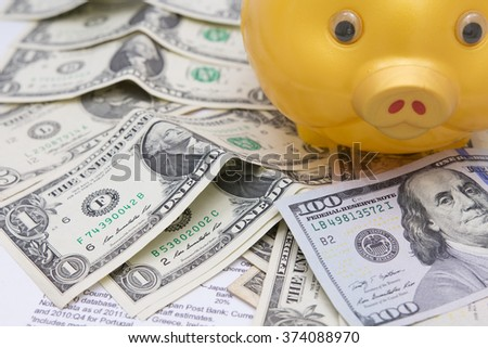 A piggy bank with money dollars  on financial report, savings - stock photo