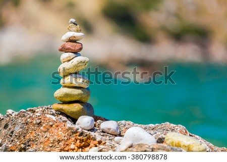 A pile of a well balanced rocks on the beach usable for simple backgrounds or balance and meditation concepts. - stock photo