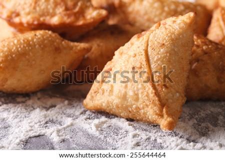 A pile of baking samosas macro on the table with flour. horizontal  - stock photo