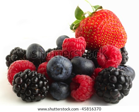 A pile of berry fruits, blueberries, raspberries, blackberries and a strawberry, against a white background. - stock photo