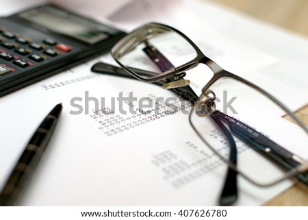 A pile of bills, checkbook, pen and calculator on the table. - stock photo