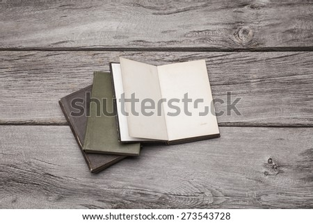 A pile of blank antique books sit on a rustic wooden background. The top book on the pile is open and can be used to display your content. - stock photo