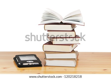 A pile of books and e-book on wood table against a white background - stock photo