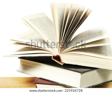 A pile of books and one open book on white background