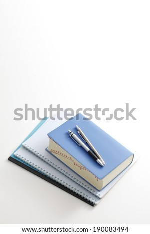 A pile of books with two silver pens. - stock photo