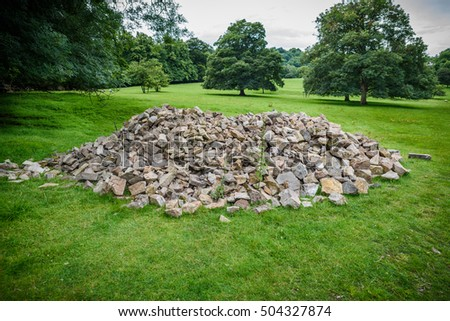 A pile of boulders in a meadow.