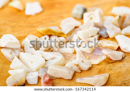 A pile of bright opal chip beads on birch wood - stock photo