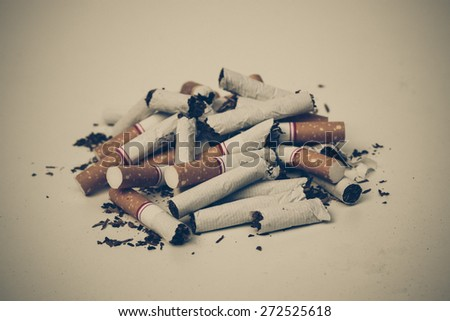 a pile of broken, destroyed cigarettes with sad tone - stock photo