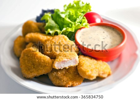 A pile of chicken nuggets on white plate with sauce and salad - stock photo