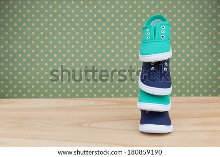 A pile of children's shoes background. Blue and green shoes on a wooden table - stock photo
