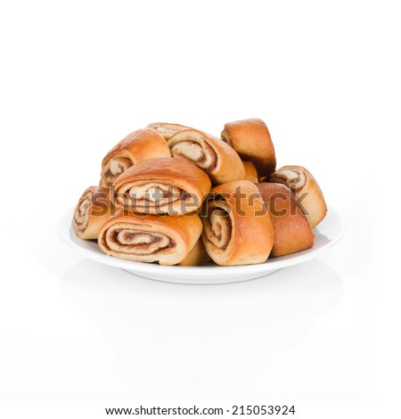 A pile of cinnamon buns on white plate - stock photo