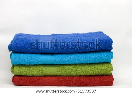 A pile of clean terry towels of different colors on a white background